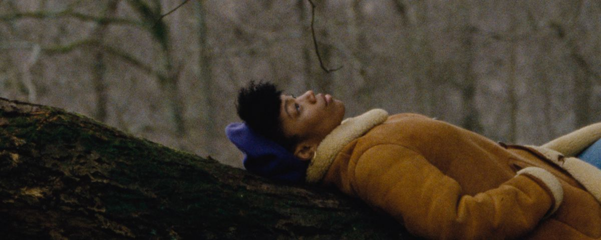 Naomi Ackie lounges on a tree branch in coat and hat in Master of None season 3