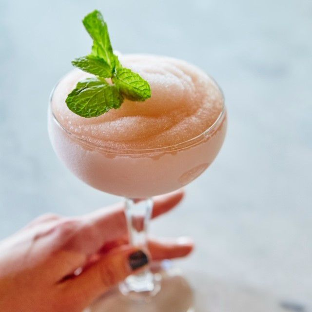 A frozen slushee cocktail in a coupe glass with a sprig of mint