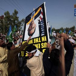 Angry protesters strike a poster showing a portrait of U.S. President Barack Obama during a demonstration near the U.S. consulate in Peshawar, Pakistan on Tuesday, Sept. 18, 2012. Hundreds of angry protesters broke through a barricade outside the U.S. Consulate in  Peshawar, sparking clashes with police that left several wounded on both sides, police said.