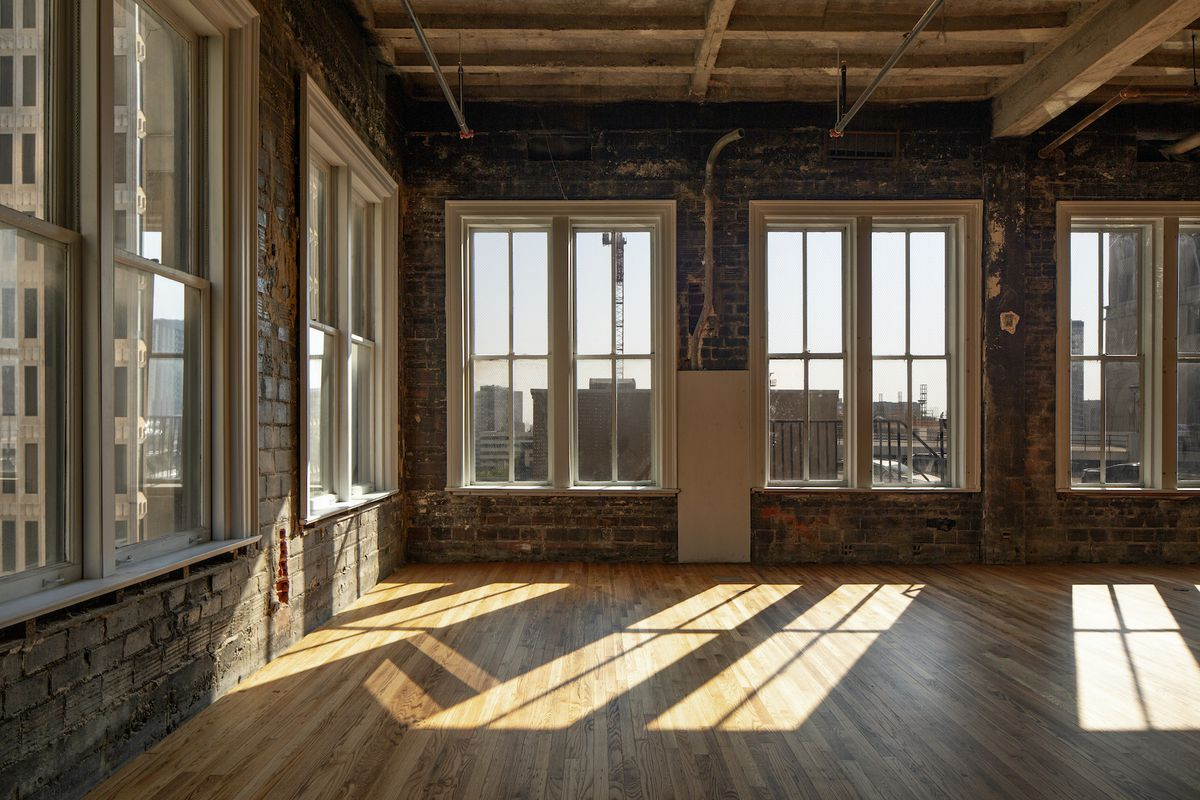 Long windows look out at the downtown skyline. Inside, the old wood floors look polished and almost new.