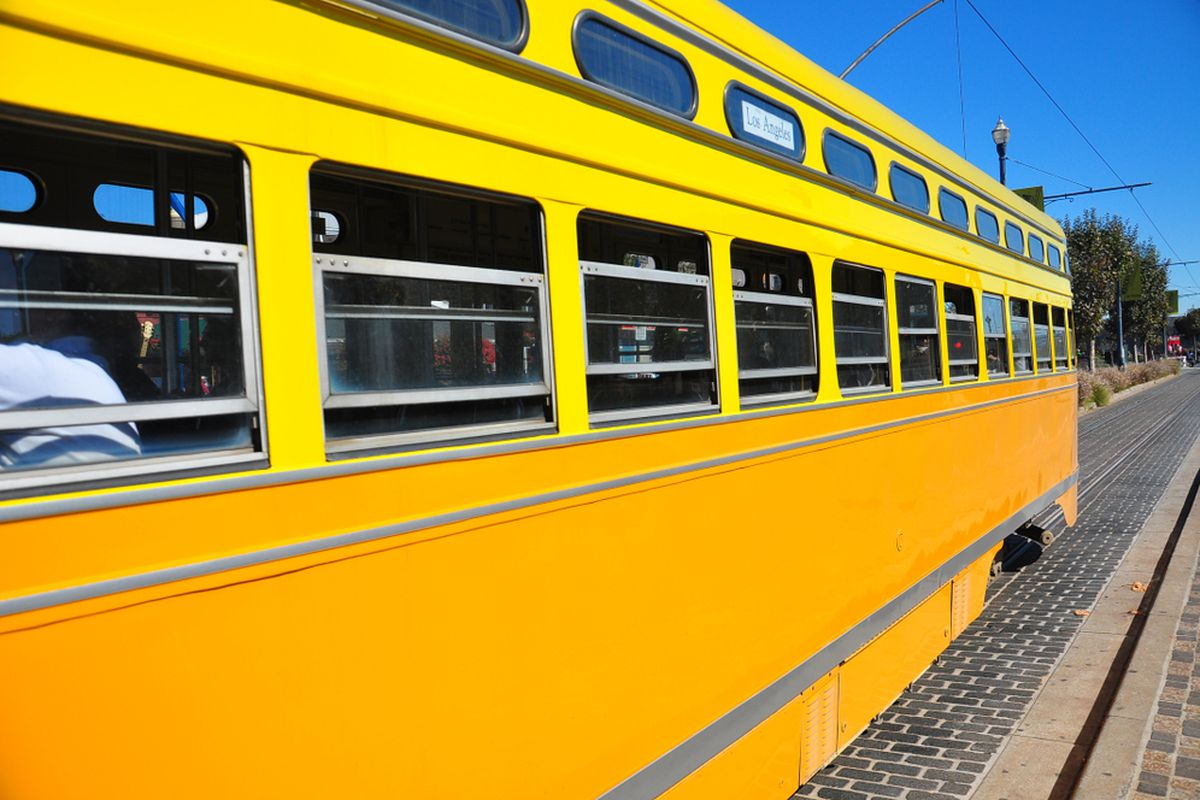 The side of a yellow Muni streetcar.