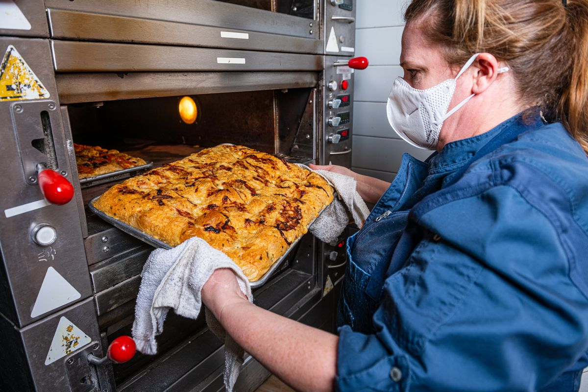 Amy Brandwein pulls a sheet of focaccia out of the oven