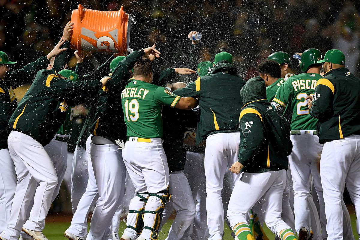 Khris Davis and his teammates of the Oakland Athletics celebrates after Davis hit a walk-off solo home run to defeat the Minnesota Twins 7-6 in extra innings at Oakland Alameda Coliseum on September 21, 2018 in Oakland, California.