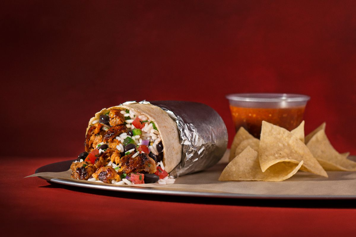 A Chipotle chorizo burrito next to a bag of chips and a plastic container of salsa, up against a red backdrop.