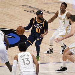 Utah Jazz guard Mike Conley (10) advances the ball upcourt as Dallas Mavericks' Tim Hardaway Jr. (11), Jalen Brunson (13), Maxi Kleber, right, and Josh Richardson (0) defend in the first half of an NBA basketball game in Dallas, Monday April 5, 2021.
