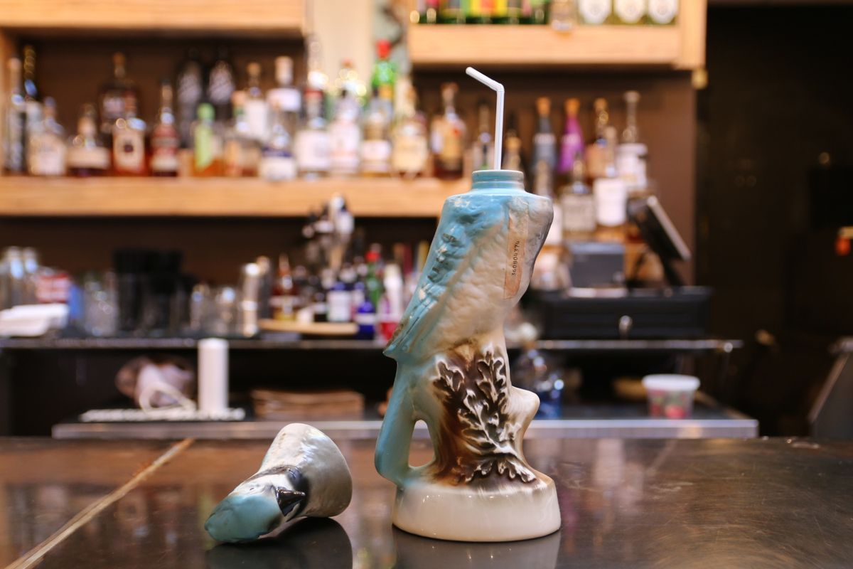 A unique piece of bar glassware —a bluejay, with the head off to the side and a straw coming out of the body. Light wooden shelves of bottles are visible in the background.