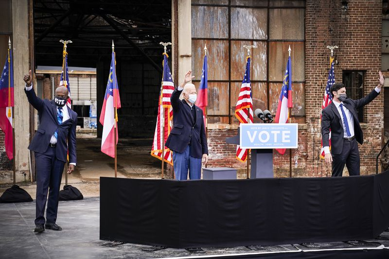 Biden, in a navy sportscoat and blue slacks, waves while standing between — and six feet from — Warnock and Ossoff. All three have on masks; Warnock and Ossoff both have on dark suits with blue ties. The three men are on a stage, outside, set up in front of an industrial building that's decorated with US and Georgia state flags.