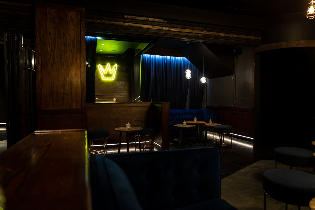 The downstairs space of the two-storey MajesThé is pictured, with dark curtains, empty tables, and neon lights included.