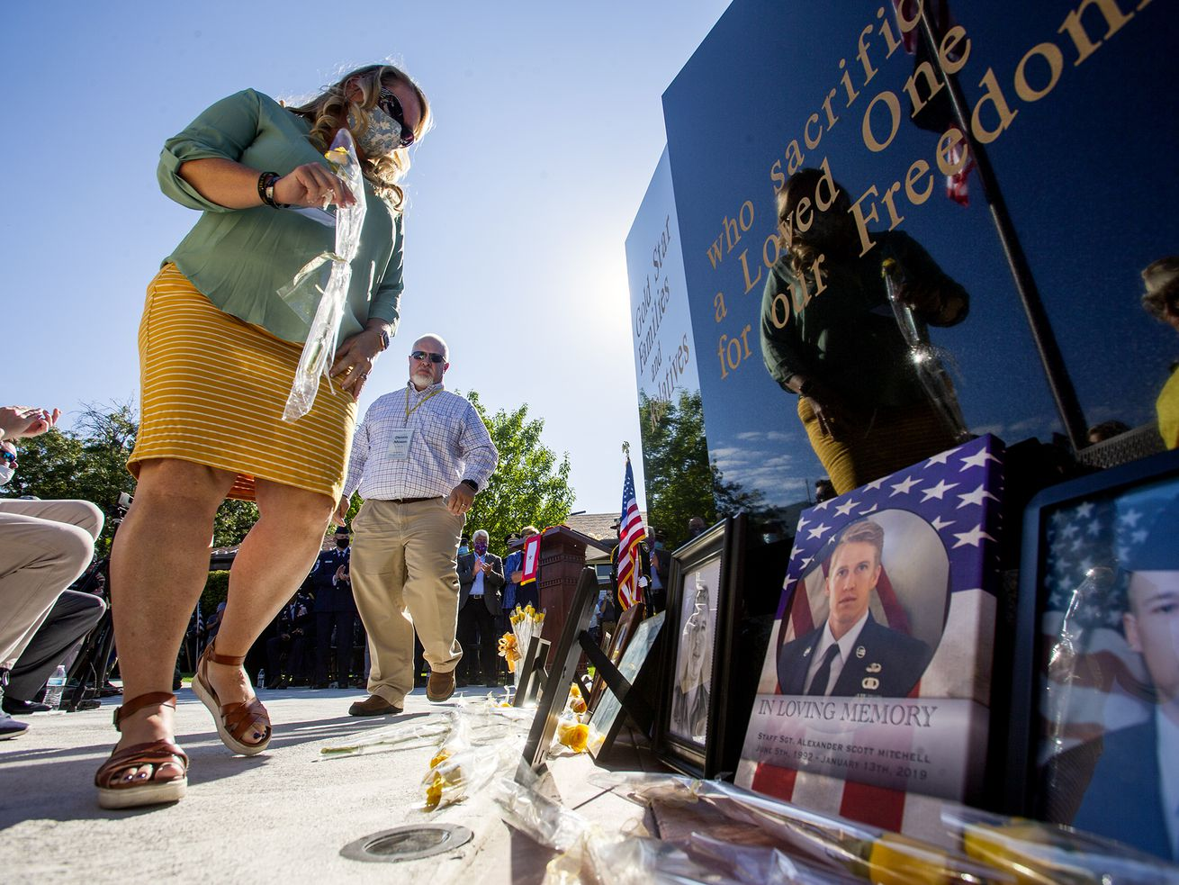 Jennifer and Dennis Moxon place a yellow rose for their son, Sgt. Douglas Lee Moxon, at the base of the new Gold Star Families Memorial in North Ogden on Saturday, Aug. 1, 2020.