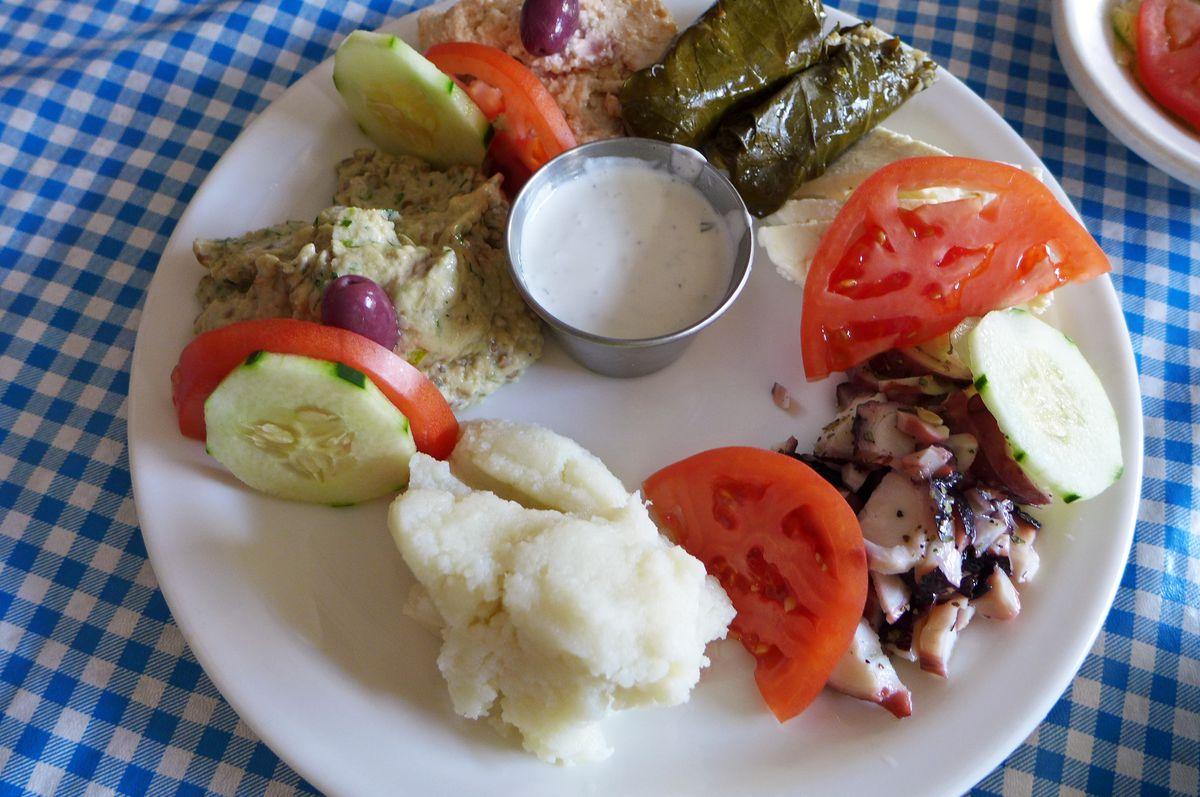 Appetizer platter include octopus, grape leaves, and skordalia.