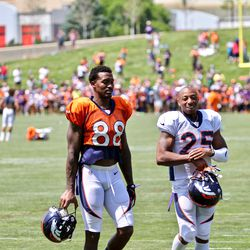 Broncos WR Demaryius Thomas (88) and Chris Harris Jr. (25) chat while walking off the field after practice.