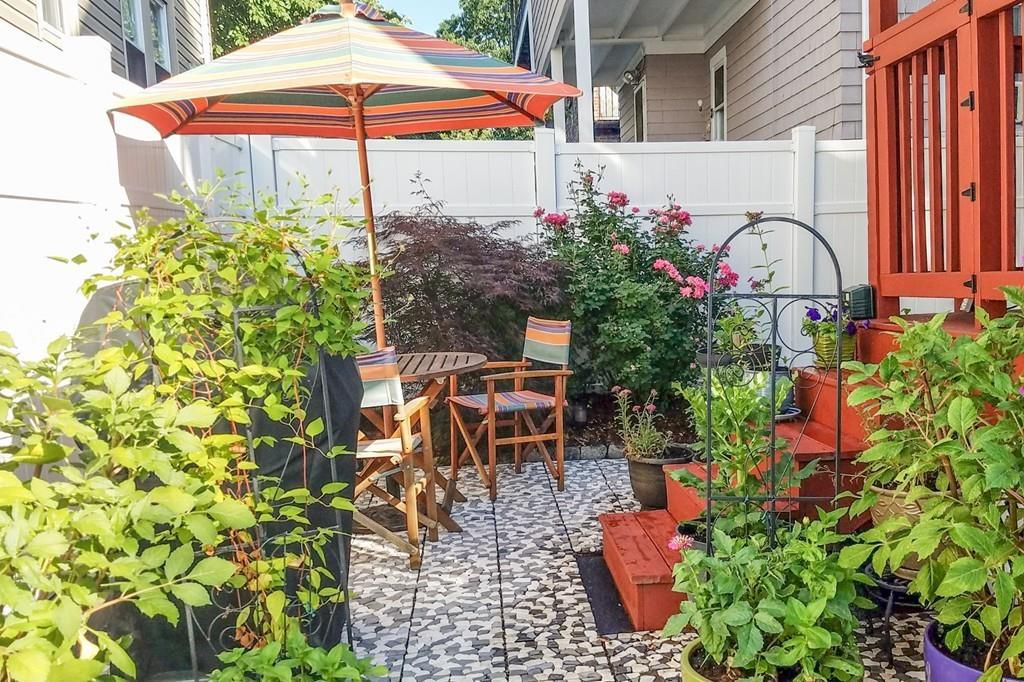 A lush, though small, outdoor patio with a table and chairs, and there's an umbrella open over the table.
