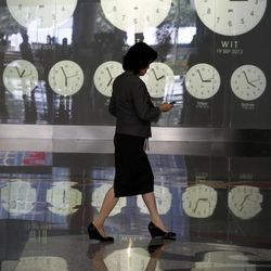 An Indonesian woman walks past clocks showing world time at the Jakarta Stock Exchange in Jakarta, Indonesia, Wednesday, Sept. 19, 2012.