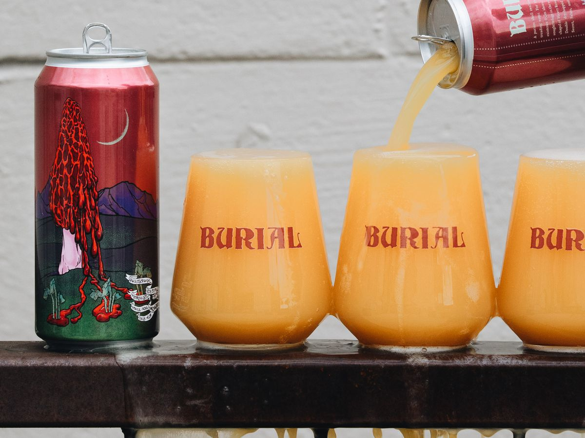 A hand pours a beer can into three glasses that overflow over the railing they're sitting on, beside another full can of the same beer with a decorative label
