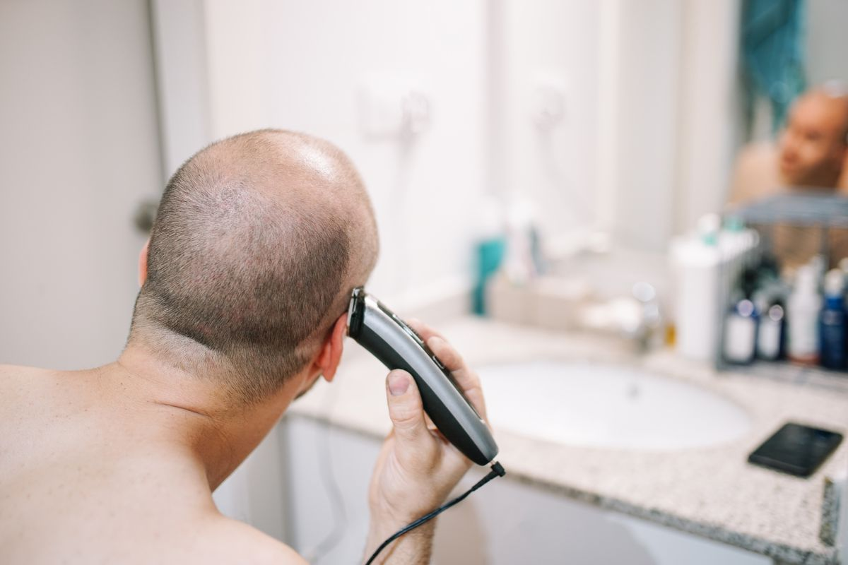 A person looking in a mirror and holding an electric shaver to their head.