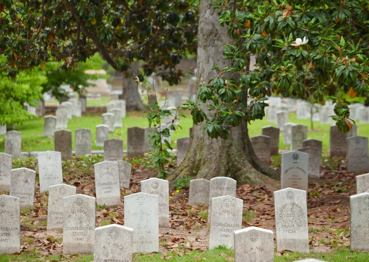 Cemetery with rows and rows of white stone headstones.