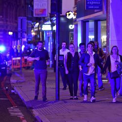 """People run down Borough High Street as police are dealing with a """"major incident"""" at London Bridge in London, Saturday, June 3, 2017."""