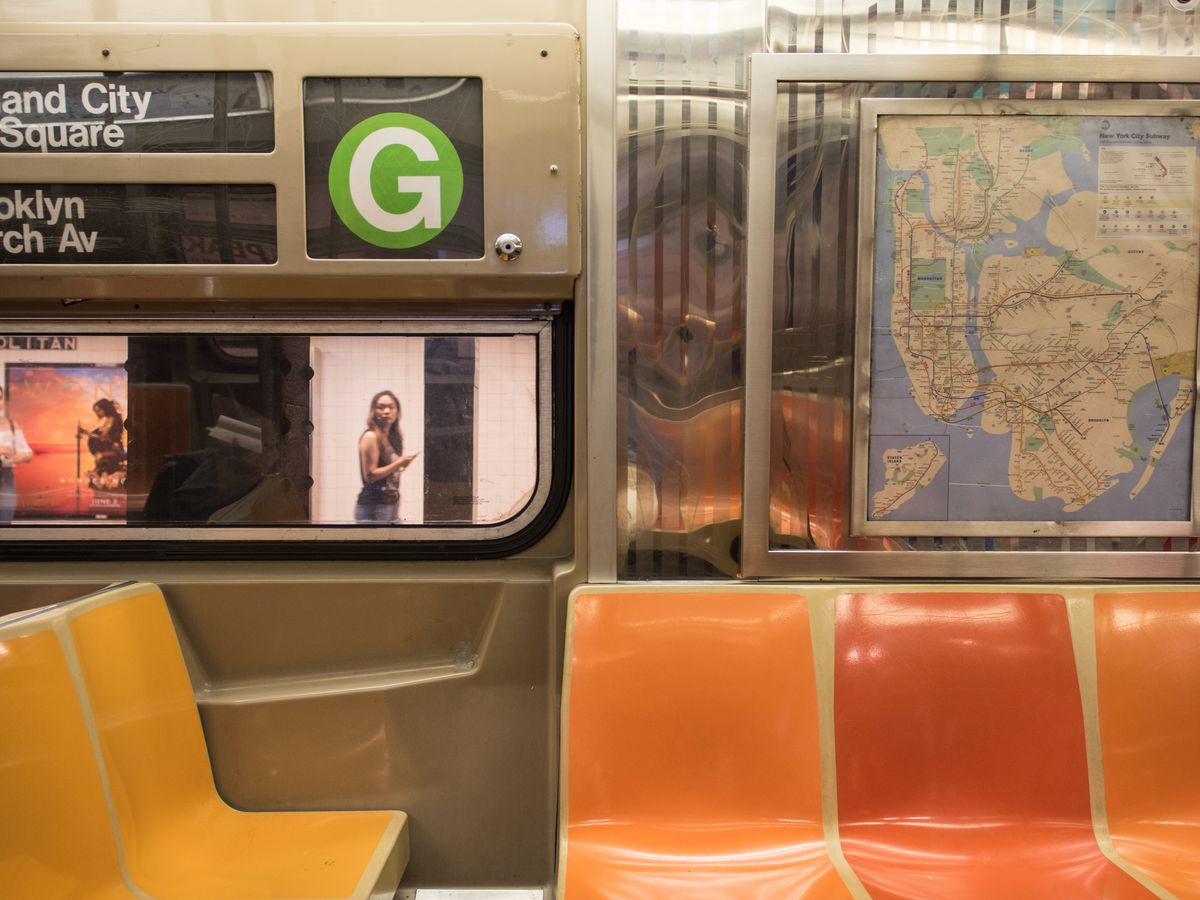The interior of the G train in New York City. The seats are orange. There is a subway map on the wall.