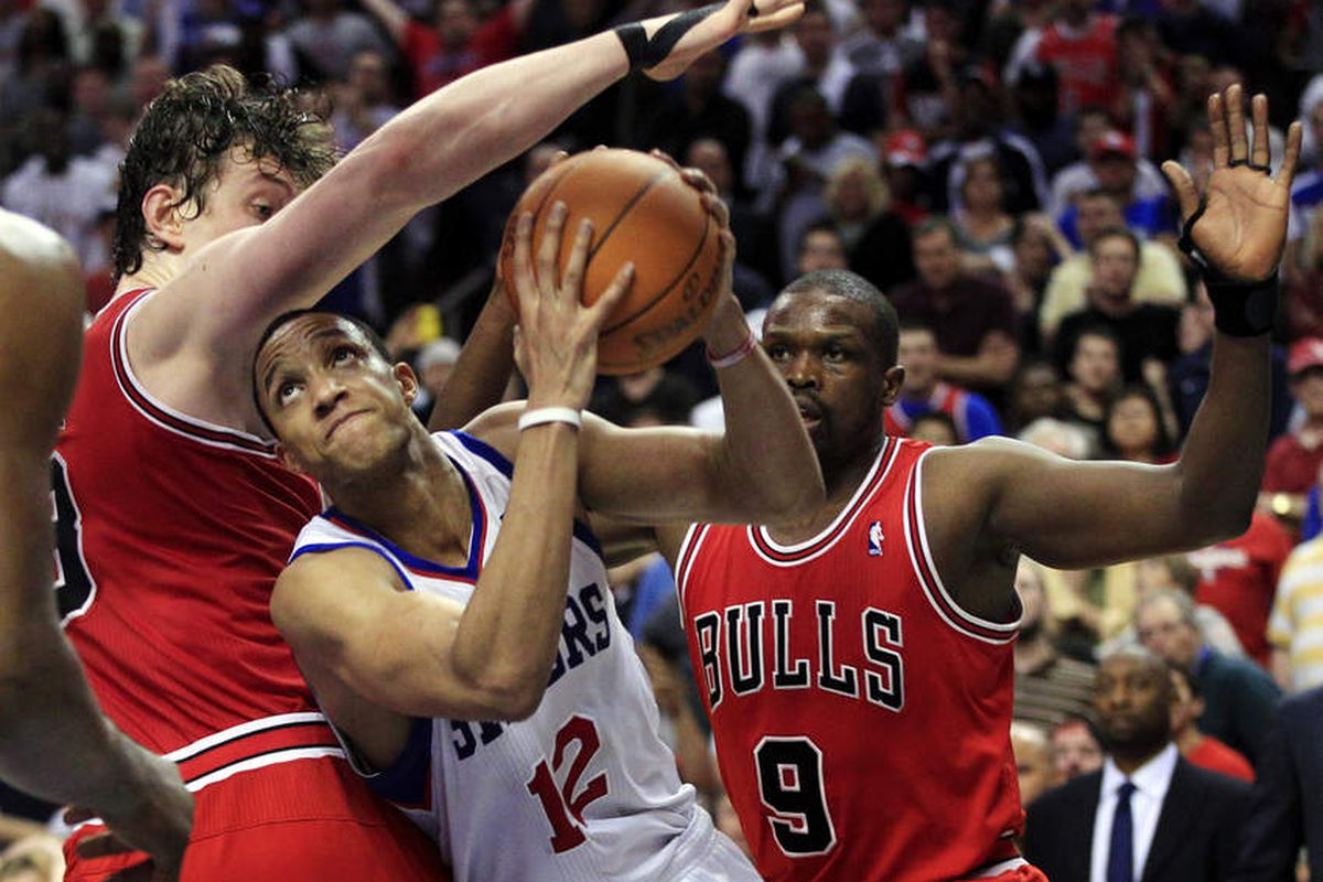 1301d94e4ce7 Philadelphia 76ers  Evan Turner (12) fights his way to the basket past Chicago  Bulls  Omer Asik