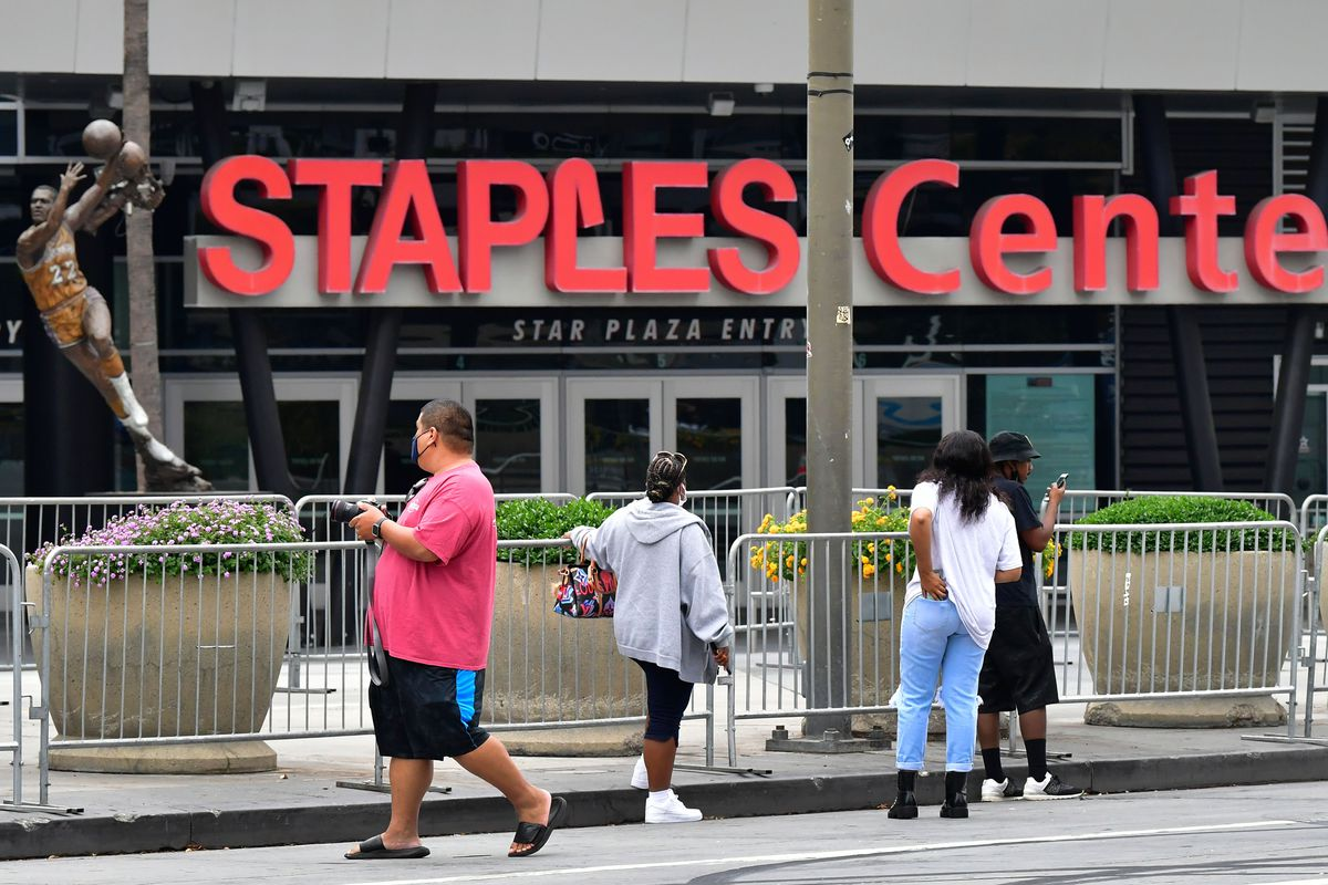Fans gather behind barricades surrounding the Staples Center in Los Angeles, California on October 9, 2020 ahead of game 5 of the 2020 NBA Finals between the Los Angeles Lakers and the Miami Heat. - Staples Center, home of the Lakers, has announced the facility will not televise Game 5 or hold any potential postgame celebrations for this year's final due to the ongoing coronavirus pandemic.