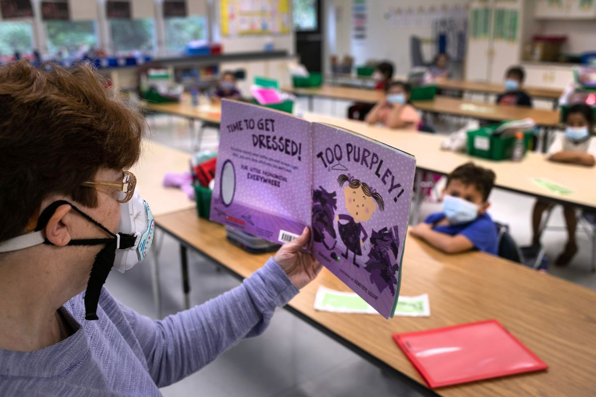 A paraeducator reads to a kindergarten class in Stamford, Connecticut in October 2020.