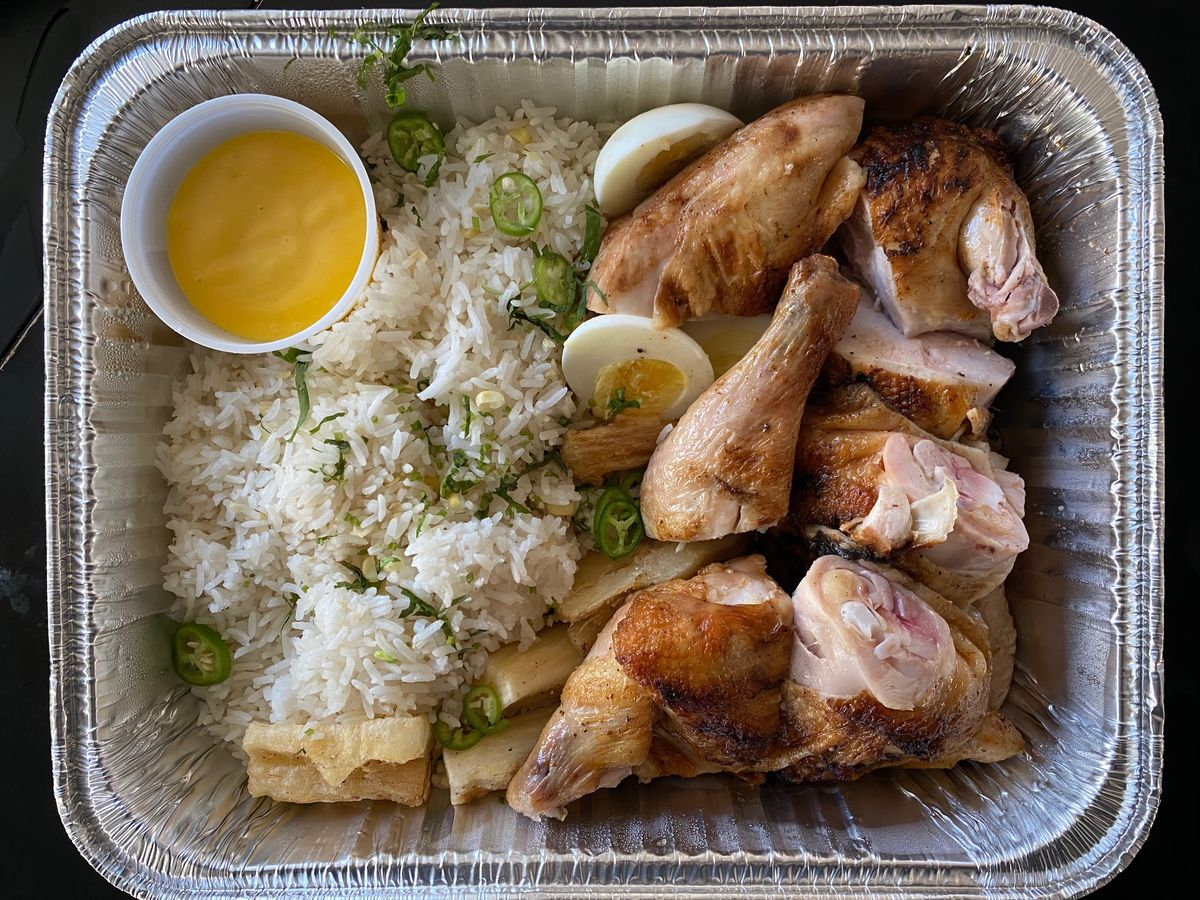 Aluminum tray filled with pieces of on-the-bone Peruvian grilled chicken, rice, fried yucca, and yellow sauce