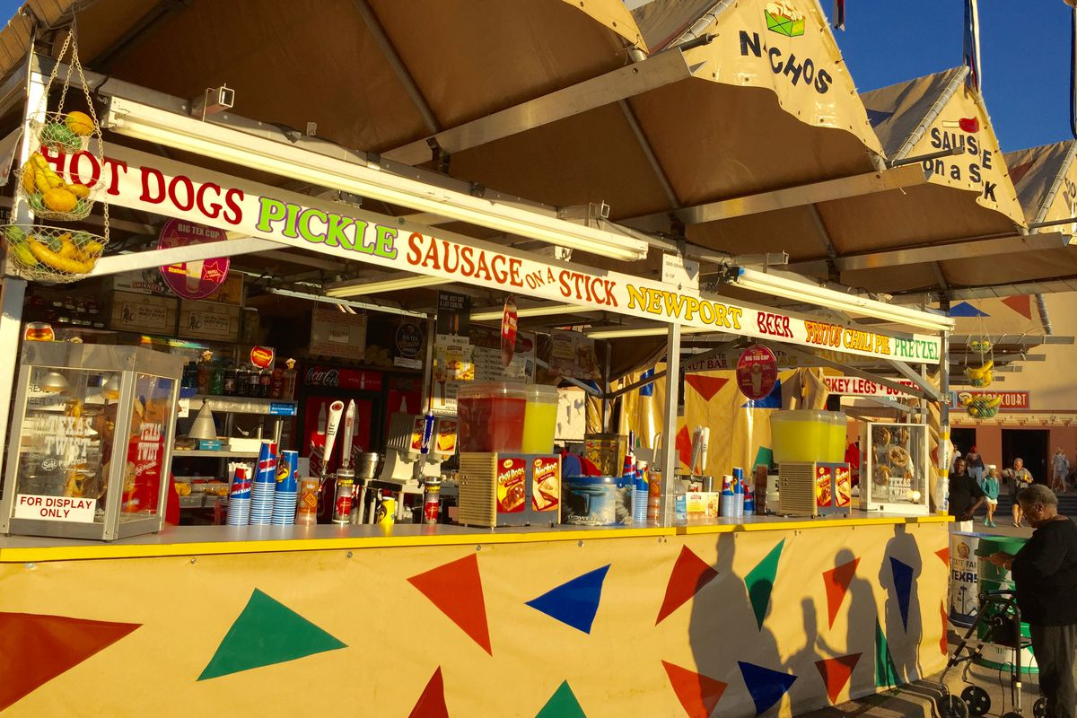 A brightly colored set of food service booths at the State Fair of Texas advertising hot dogs, pickles, sausage, and other foods.