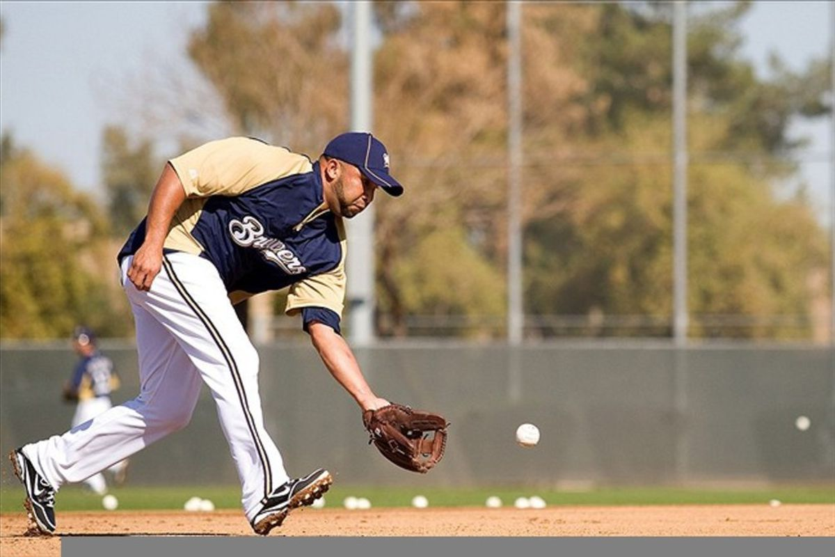 Feb 26, 2012; Phoenix, AZ, USA; Milwaukee Brewers shortstop Alex Gonzalez (11) fields a grounder during a workout during spring training at Maryvale Baseball Park.  Mandatory Credit: Jake Roth-US PRESSWIRE