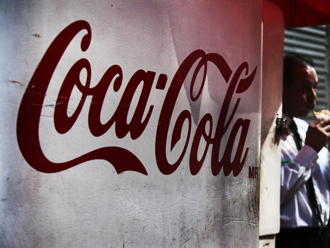 A man stands next to a Coca-Cola sign in Mexico City, on December 2, 2015.