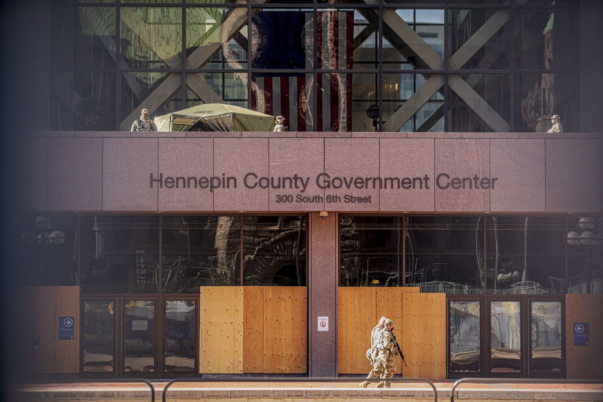 Men in camouflage with rifles walk past the boarded up doors of the Hennepin County Government Center. On a balcony of the building, more people in military uniforms stand guard.