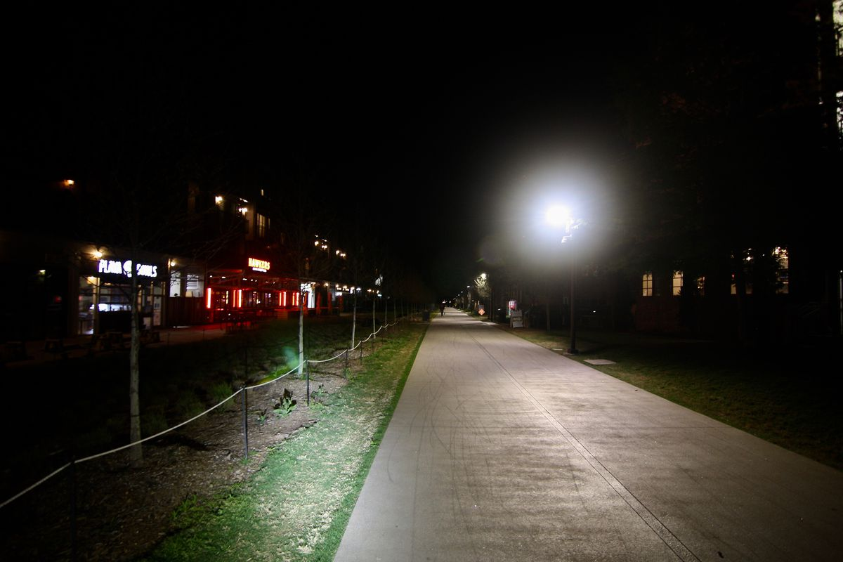 An empty concrete trail seen at night with lights all around it.