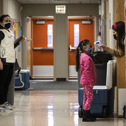 A preschool student gets her temperature checked as she walks into Dawes Elementary School at 3810 W. 81st Pl. on the Southwest Side, Monday morning, Jan. 11, 2021.