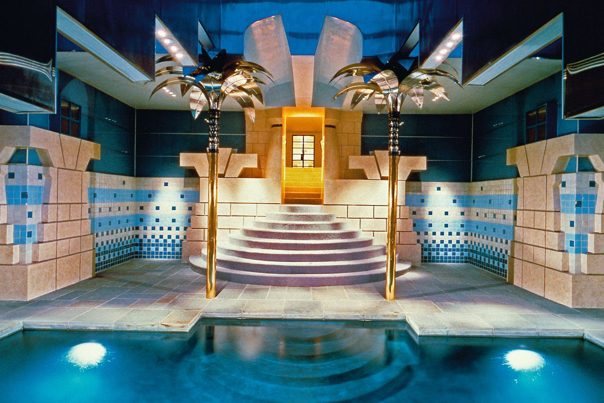 The inside of a pool house with silver palm trees as architectural columns, tiled walls, and a dramatic cone-shaped staircase leading to the blue pool.