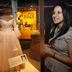 """Singer Natalia Flores, 20, of Chicago, stands next to her Quinceanera dress from 2006 that is on display as part of the new exhibit, """"American Stories,"""" at the Smithsonian National Museum of American History in Washington, on Wednesday, April 11, 2012. The National Museum of American History will open a new exhibit featuring iconic objects from pop culture along with objects dating back to the Pilgrims' arrival in 1620. """"American Stories"""" will be a new chronology of U.S. history from the first encounters of Europeans and Native Americans to the 2008 presidential election."""