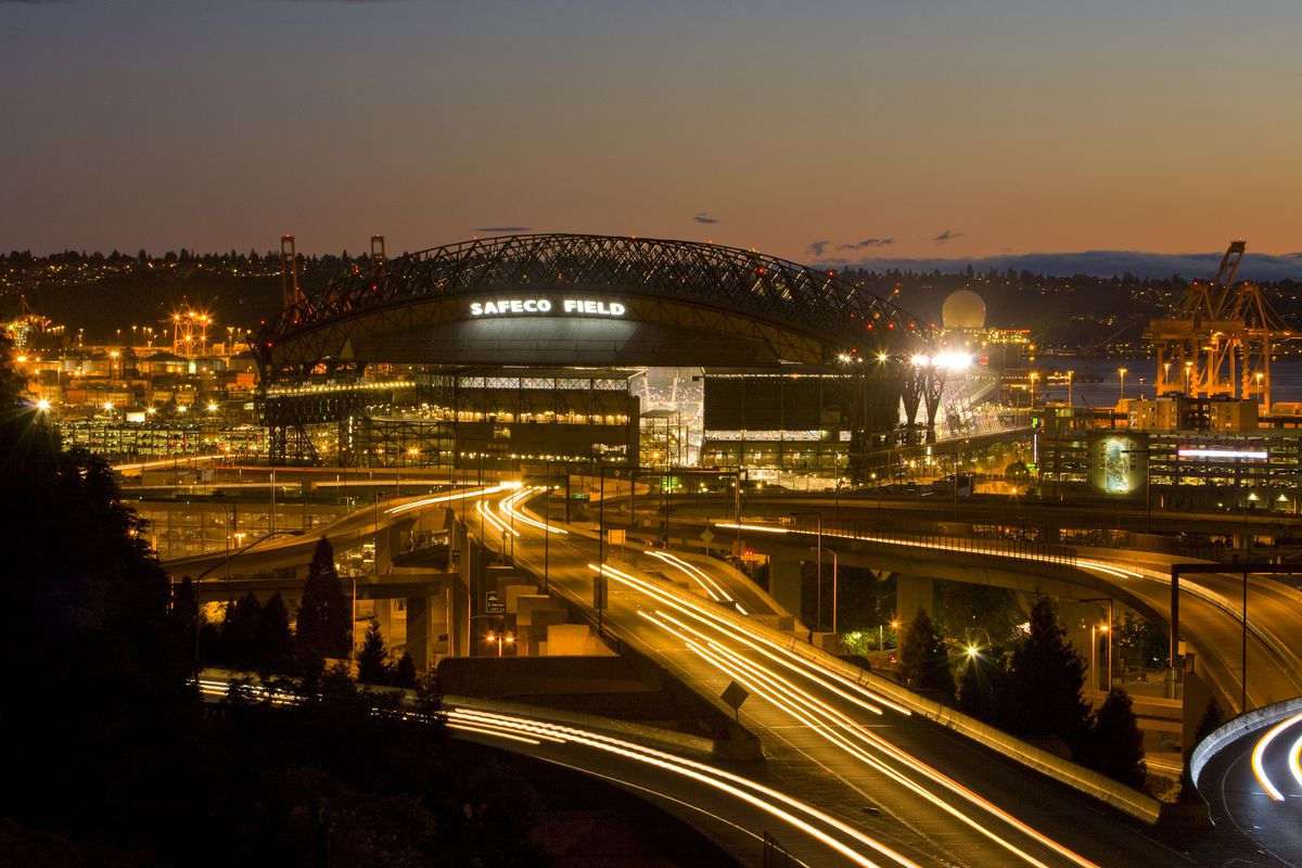 Safeco Park at Sunset, in a time lapse photograph showcasing the streaking headlights on the highway interchange outside of the stadium