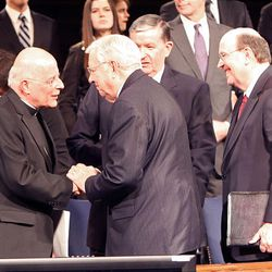 Cardinal Francis George, left, greets LDS apostles Elders M. Russell Ballard and Quentin L. Cook, right, and BYU President Cecil O. Samuelson Tuesday following Cardinal George's remarks at a BYU devotional.