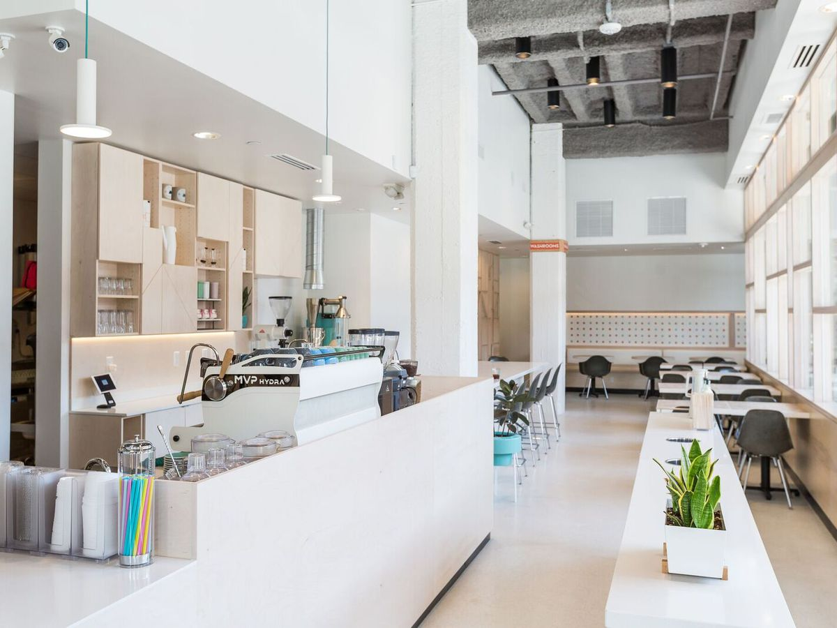 An extremely bright white, minimalist cafe with a white espresso machine, white counters, white light fixtures, and white tables.