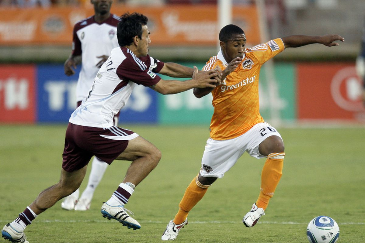 HOUSTON - MAY 04:  Corey Ashe #26 of the Houston Dynamo is grabbed by Pablo Masatroeni #25 of the Colorado Rapids at Robertson Stadium on May 4, 2011 in Houston, Texas.  (Photo by Bob Levey/Getty Images)