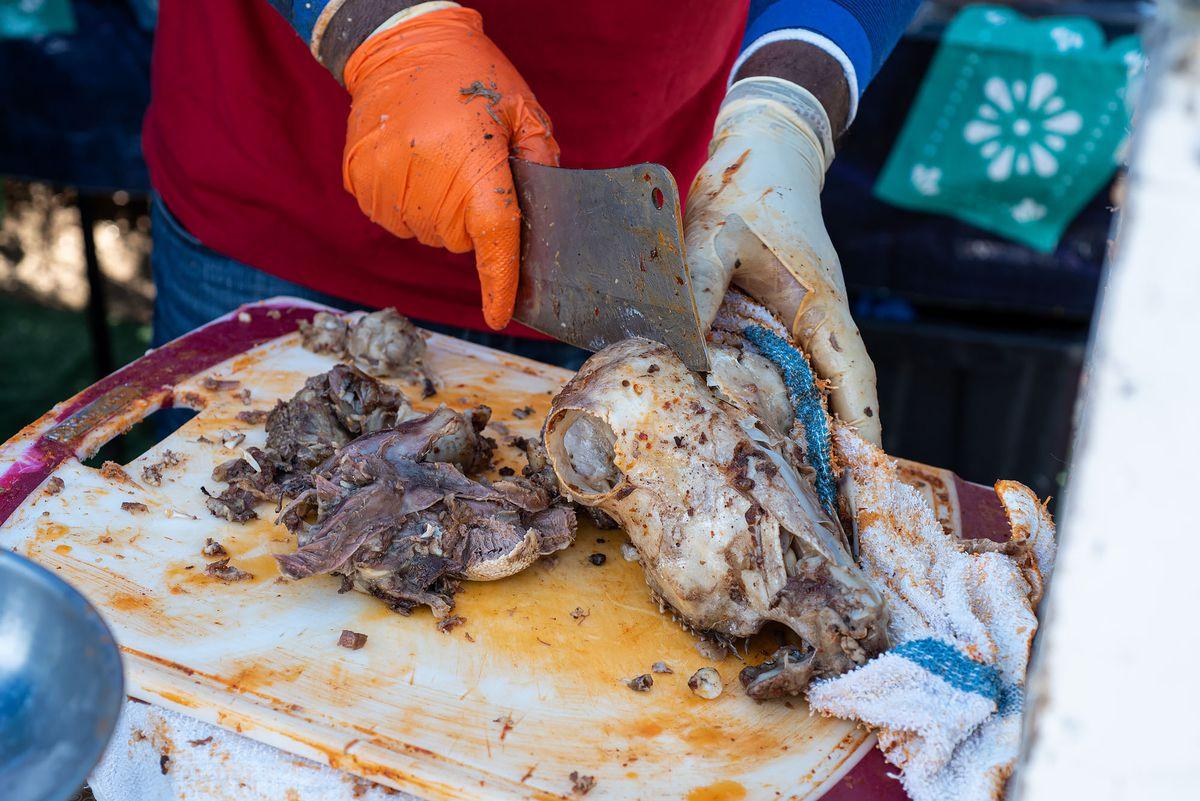 Splitting a lamb head with a butcher's knife.