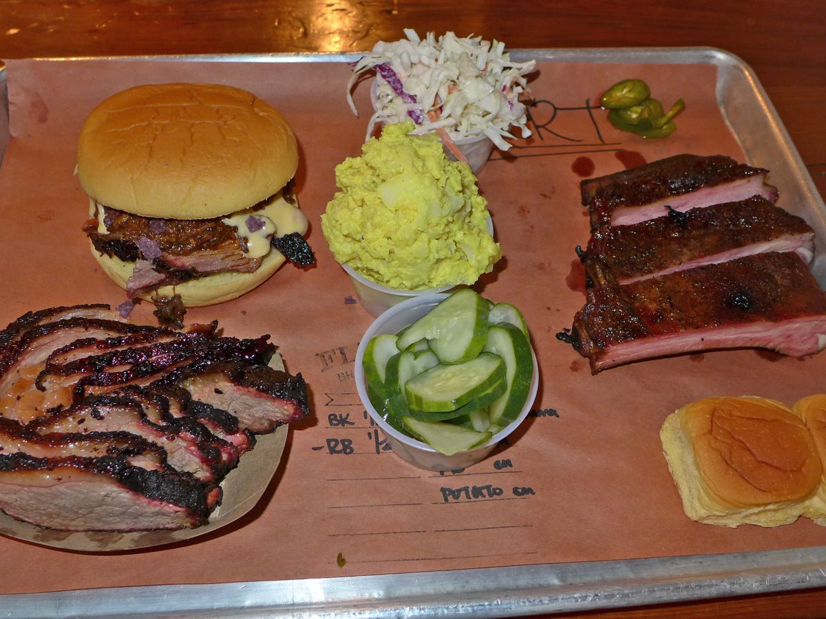 On brown paper ribs, brisket blackened at the edges and some very yellow potato salad are seen.