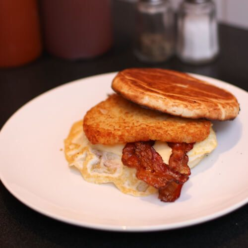 Fried egg, bacon, and hash brown on a Portuguese muffin