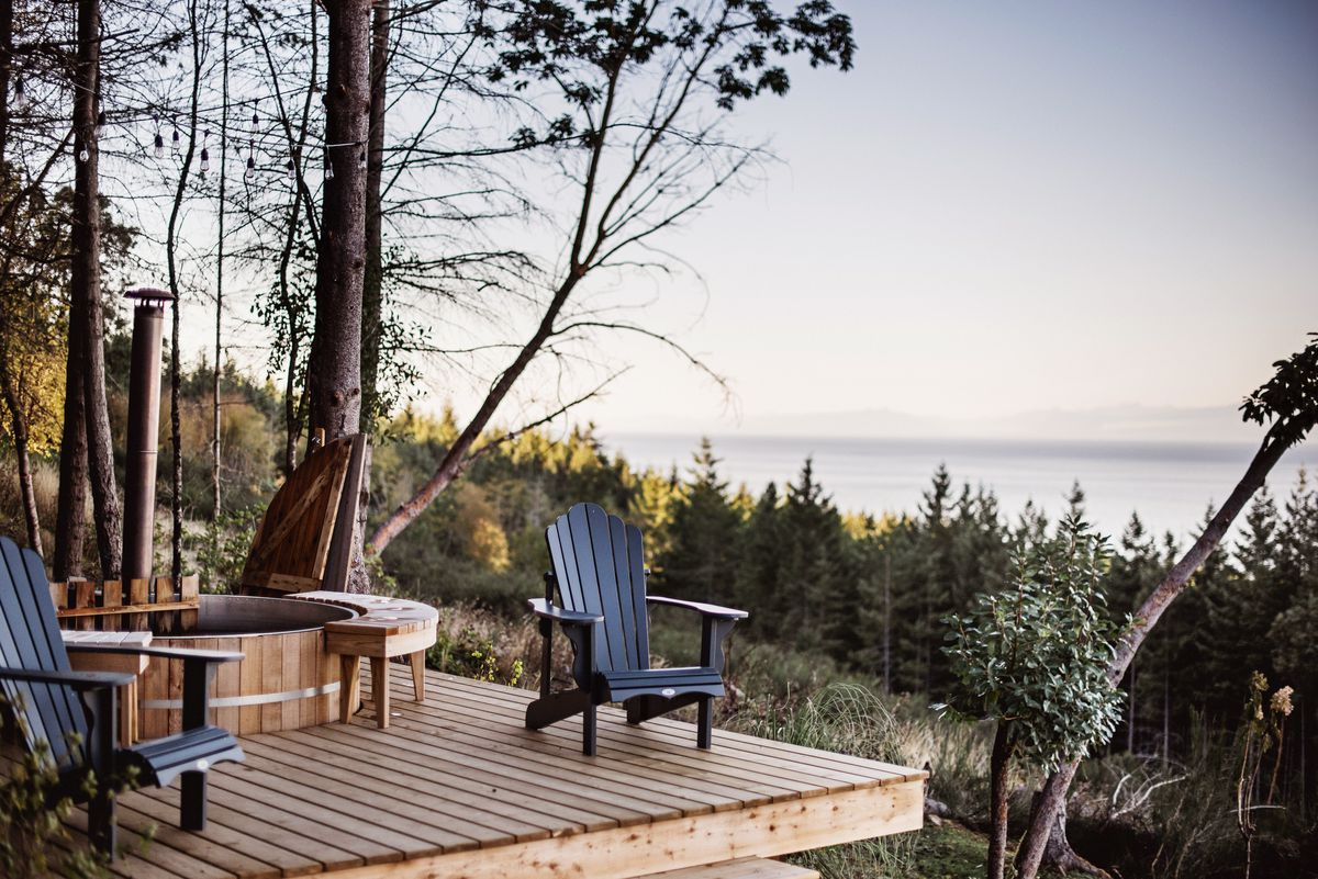 A wooden deck with built-in hot tub overlooks a forest and water views.