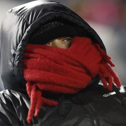 A San Diego State fan tries to keep warm during an NCAA college football game against San Diego State and BYU Saturday, Dec. 12, 2020, in Provo, Utah.