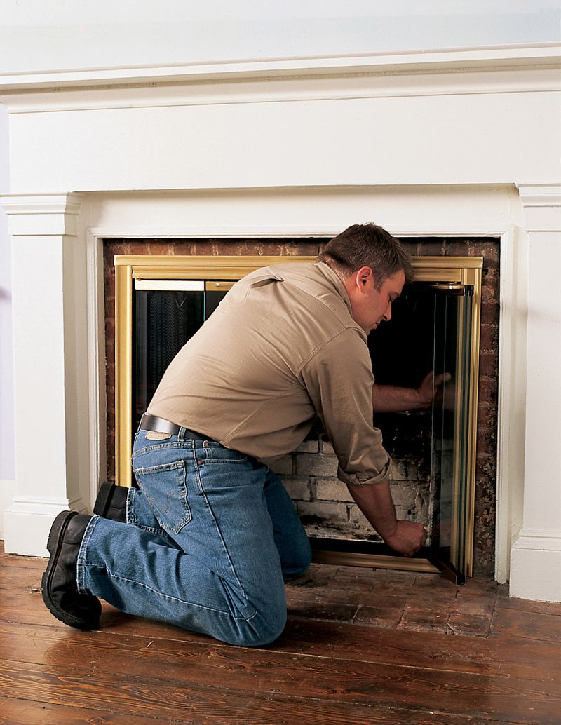 Person adding markers around fireplace doors.