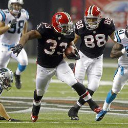 Atlanta Falcons running back Michael Turner (33) runs away from Carolina Panthers cornerback Captain Munnerlyn (41) and  free safety Haruki Nakamura (43) on a second half touchdown run in an NFL football game Sunday, Sept. 30, 2012, in Atlanta.