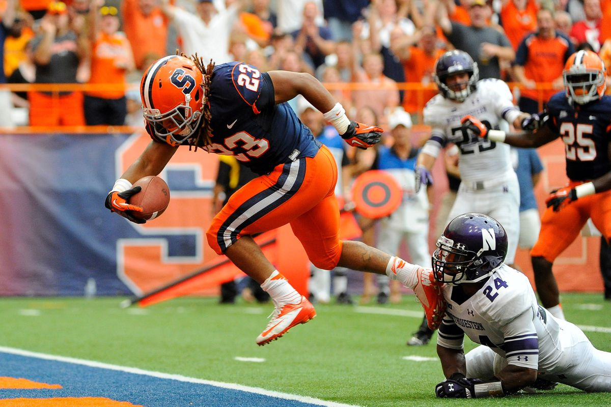 Syracuse running back Prince-Tyson Gulley breaks the tackle of Northwestern Wildcats defensive back Ibraheim Campbell at the Carrier Dome.