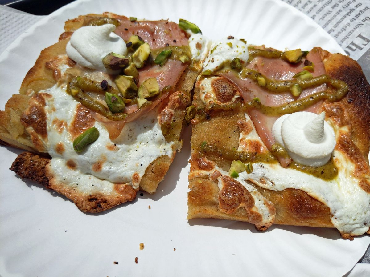 Two square slices of pizza on a paper plate topped with greens, mozzarella cheese.