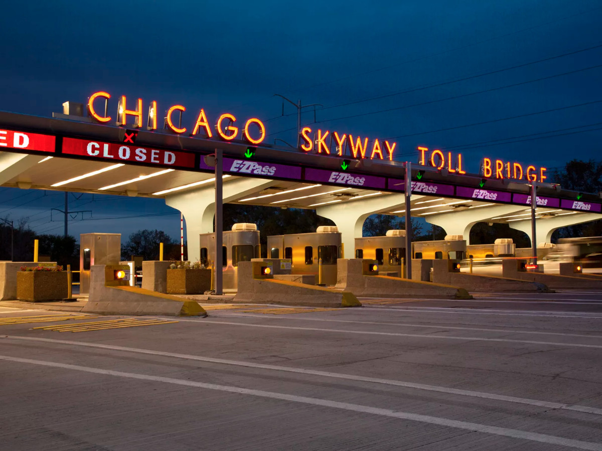 An image of a neon sign over a tollway road that reads: Chicago Skyway.