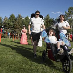 Joe Reardon and Anita Reardon run with their daughter, JulieLynn Reardon, during the Fairy Tale 5K at Thanksgiving Point in Lehi Saturday, June 21, 2014. In spite of being diagnosed with a severe form of epilepsy, JulieLynn Reardon is on grade level in most subjects.