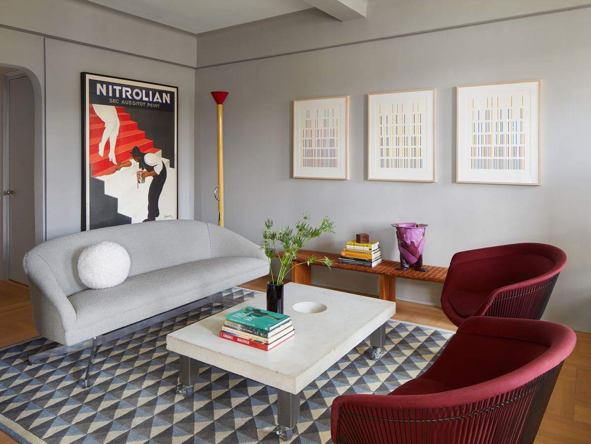 A living room. The walls are painted light grey. There is a grey couch, white coffee table, and two dark red arm chairs. There is an area rug which has a grey and white pattern. Multiple framed works of art hang on the walls.